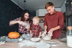 Dad, mom and little son cook a pie Royalty Free Stock Images