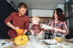 Dad, mom and little son cook a pie Royalty Free Stock Image