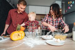 Dad, mom and little son cook a pie Royalty Free Stock Photography