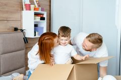 Dad mom and little son play in the bedroom with paper boxes. Happy family concept stock photo