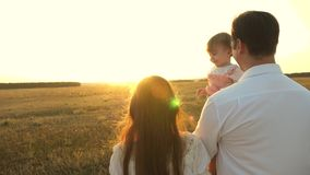 Dad and mom playing with a little daughter in her arms at sunset. family walks with a child at sunset. father playing. Dad and mom playing with little daughter royalty free stock photo