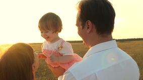 Dad and mom playing with a little daughter in her arms at sunset. family walks with a child at sunset. father playing