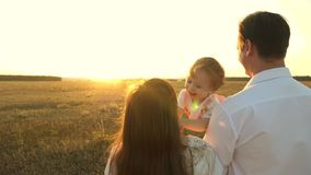 Dad and mom playing with a little daughter in her arms at sunset. family walks with a child at sunset. father playing. Dad and mom playing with little daughter royalty free stock photography
