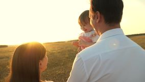 Dad and mom playing with a little daughter in her arms at sunset. family walks with a child at sunset. father playing. Dad and mom playing with little daughter stock photography