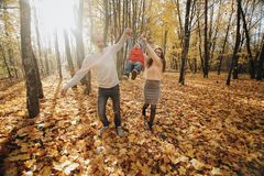 Dad and mom raised their son upside and walking along the park path. Happy family resting in the park in sunny day. stock photo