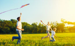 Dad, mom and son child flying a kite in summer nature. Happy family in summer nature. Dad, mom and son child flying a kite Stock Photo