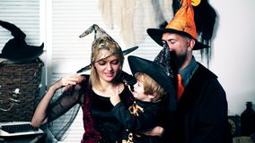Dad with mom and their son in hats and halloween suits have fun on halloween. Halloween party and celebration concept stock video footage
