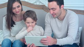 Dad, mom and their young son having fun by playing together with a tablet sitting on a couch. Professional shot on BMCC RAW with high dynamic range. You can Royalty Free Stock Image