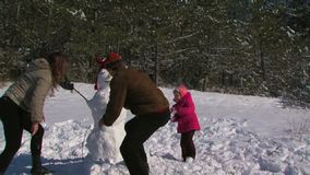 Dad, mother and little daughter make a snowman in the meadow near the forest. Mother and father with cute little daughter make three snowman in winter stock footage