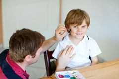 Dad painting flag on face of little kid for football or soccer Stock Photo