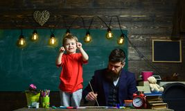 Dad painting while kid is playing. Little boy showing his fists standing next to his busy daddy. Concentrated father and. Playful child Royalty Free Stock Photos