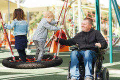 Dad play with son and daughter. Disabled Father play with his little son and daughter stock photos