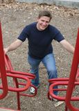 Dad at Playground. Handsome father waits for his kids to come down on the monkey bars at a playground Stock Photography