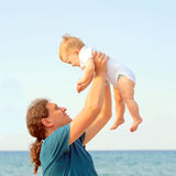 Dad playing with baby on the beach. Royalty Free Stock Images
