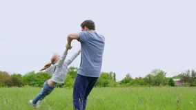 Dad playing with daughter in the field, tosses and circles. fun with the family outdoors.
