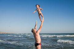 Dad is playing with his daughter throwing her up into the sky, on a sea beach on a bright sunny hot day Royalty Free Stock Photos