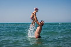 Dad is playing with his daughter throwing her up into the sky, on a sea beach on a bright sunny hot day Royalty Free Stock Image