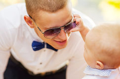 Dad playing with his son. The son is played with sunglasses Royalty Free Stock Photo