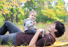 Dad playing with son on autumn outdoor. Young dad playing with son on autumn outdoor Royalty Free Stock Image