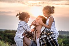Dad playing with two little cute daughters royalty free stock photography
