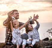 Dad playing with two little cute daughters stock images