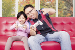 Dad playing video game with his daughter Stock Photos