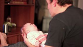 Dad plays with the baby. Father lying on a couch holds his baby son in his lap stock footage