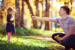 Dad plays with daughter in summer park. Dad plays with daughter in sunny park Royalty Free Stock Image