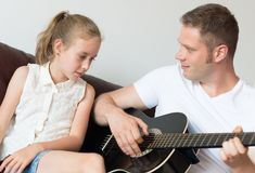 Dad plays the guitar. Dad plays the guitar for his daughter royalty free stock images