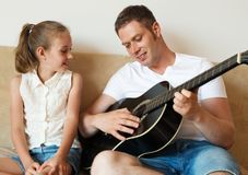 Dad plays the guitar. Dad plays the guitar for his daughter royalty free stock photos
