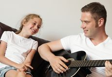 Dad plays the guitar. Stock Photography