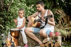 Dad plays the guitar, daughter on the nature royalty free stock photos