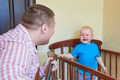 Dad plays guitar to console his crying son. Dad plays guitar to console his crying little son stock images