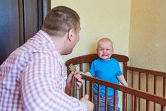 Dad plays guitar to console his crying son. Dad plays guitar to console his crying little son royalty free stock photography