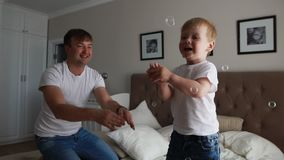 Dad plays with his son in the bedroom catching soap bubbles smiling and laughing stock video footage