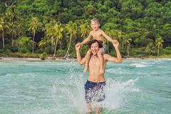 Dad plays with his son in the sea.  stock images