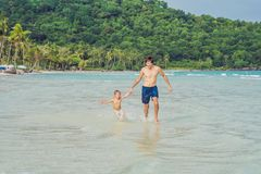 Dad plays with his son in the sea.  stock image
