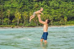Dad plays with his son in the sea.  stock photos