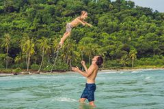 Dad plays with his son in the sea.  stock photo