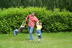 Dad plays with young children stock photo