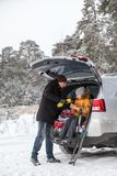 Dad pouring hot tea for girl after sports activities such as skiing. Sitting in trunk of suv with opened back door at winter seaso. Dad pouring hot tea for girl Royalty Free Stock Image