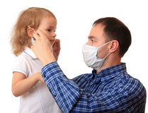 Dad puts a medical mask on to daughter. Royalty Free Stock Images