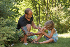 Dad puts plaster on sons elbow royalty free stock photos