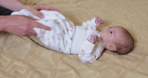 Gymnastics with the baby. Dad raises the arms of a baby to train the gymnastics stock footage