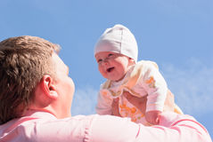 Dad raises his joyous baby Stock Photography