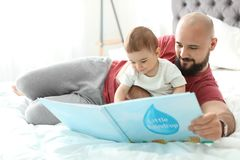Dad reading book with his little son. In bedroom stock images