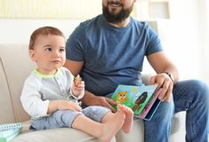 Dad reading book with his little son. In living room royalty free stock image