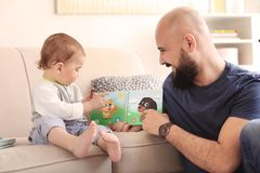 Dad reading book with his little son. In living room royalty free stock photos
