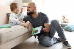 Dad reading book with his little son. In living room royalty free stock photo