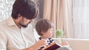 Dad reading book his son. Do you like this book. Smiling young man sitting with his son on couch in living-room and reading him his favorite book stock video footage